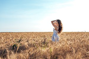 Beautiful happy woman field, sunny afternoon, white dress. Brunette hair, tanned skin, concept of enjoying nature. Happy smiling. Harmony with wheat.