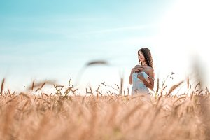 Beautiful happy woman in a field, sunny afternoon, white dress. Beautiful hair, tanned skin, concept of enjoying nature. Rest on the air. Harmony with wheat. Blue sky.