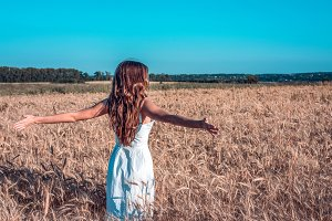A girl in summer in a wheat field, raises her hands in a white dress, tanned skin, happy on vacation fresh air. A sunny day. Enjoying nature. Freedom of choice.