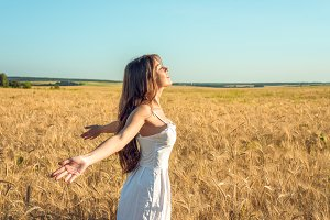 A girl in summer wheat field, raises her hands in a white dress, tanned skin, happy on vacation fresh air. A sunny day. Enjoying nature. Freedom of choice.