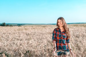 Beautiful happy girl in the field, sunny afternoon, shorts shirt. The concept of enjoying nature. Rest on the air. Walking through the meadows in wheat in the summer. Beautiful hair Happy smiling