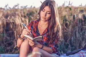 Beautiful happy brunette girl in a field, shirt. Concept new ideas, writing in notebook. Rest on air. The student conducts a personal diary of the idea.