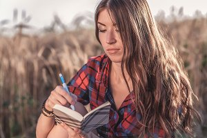 Beautiful brunette girl field, shirt. Concept new ideas, writing in notebook. A woman writes in a notebook. The journalist reads a diary of the note.
