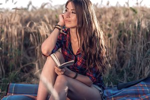 Beautiful brunette girl in the field, shirt shorts. Concept new ideas, dreams and fantasies. Happy in fresh summer in nature. In his hand a notebook, long hair, in a field.