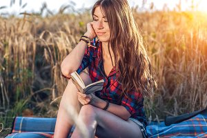 Beautiful brunette girl in field, shirt shorts. Concept of new ideas, Happy in the fresh summer in nature. In his hand a notebook, long hair. To study notes in the diary.