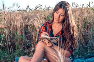 Beautiful brunette girl in field. Concept new ideas, reads notes in the fresh summer in nature. In his hand a notebook, long hair. To study notes in diary.