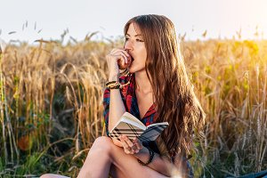 Beautiful brunette girl field. He eats an apple. Concept new ideas, outdoors, summer in nature. In his hand a notebook, long hair. Clever ideas. Inspiration by creativity.