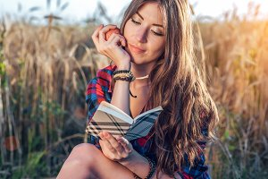 Beautiful girl student field. In his hand apple. Concept new ideas, outdoors, summer in nature. In hand notebook, long hair. Clever ideas. Inspiration by creativity. Reads the diary.