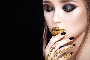 Beauty Woman Portrait. Professional Makeup and Manicure with gold foil  glitter, smokey eyes. Black colors. Copy-space