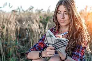 Beautiful girl student field. Journalist. Concept new ideas, summer in nature. In his hand he writes notebook, long hair. Clever ideas. Inspiration by creativity. Reads the diary.