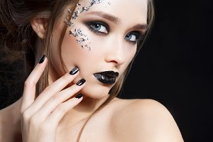Beauty Woman Portrait. Professional Makeup and Manicure with silver foil glitter, smokey eyes. Black colors. Copy-space