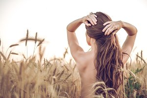 A beautiful girl wheat field, topless nude corrects long hair, a concept of purity. Outdoors. Close-up, femininity tenderness tanned skin.
