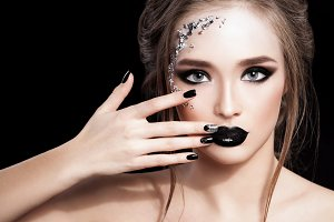 Beauty Woman Portrait. Professional Makeup and Manicure with siver foil glitter, smokey eyes. Black colors. Copy-space