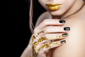 Beautiful Fashion woman model face portrait with gold lipstick and black nails. Glamour girl with bright makeup. Beauty female. Perfect skin and make up. Nail polish