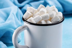 Marshmallows on blue background with copyspace