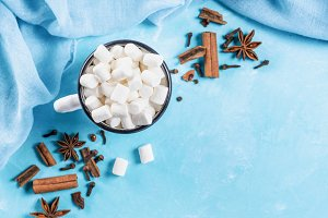 Marshmallows and winter spices on blue background