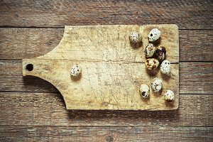 quail eggs on an old board on a wooden background