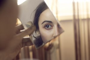 a woman makes herself makeup looking in the mirror