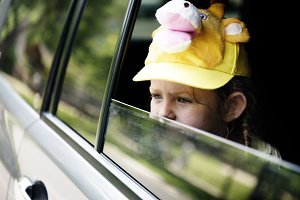 Young girl sitting inside a car