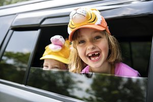 Girls smiling head out of the car