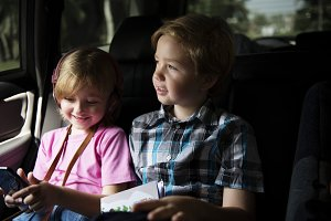 Girl sitting inside car with brother