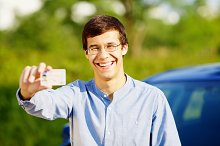 Happy young man showing his driving