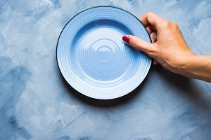 Blue background with plate and woman's hand