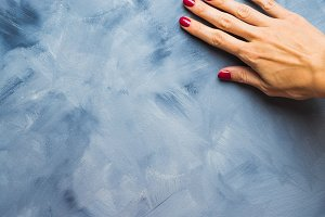 Blue pastel color background with woman's hand
