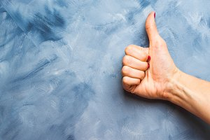 Blue background with woman's hand thumb up