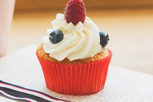 Cupcake with raspberry and blueberry, cup of hot cappuccino