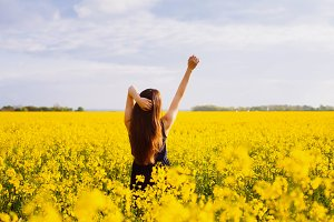 Girl enjoying sun on rapeseed meadow