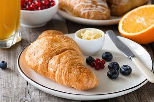 Croissants with orange juice, butter, jam and fresh fruits