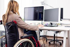 Woman Sitting In Wheelchair Working In Modern Office