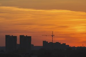 Construction cranes near residential apartments - view on sunrise, horizontal