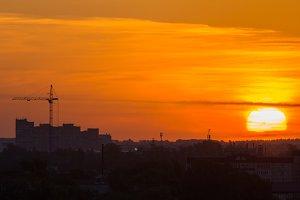 Sunrise over city skyline - red sun, construction crane, silhouette