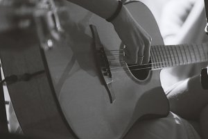 Musician in night club - guitarist plays blues acoustic guitar, extremely close up - black and white
