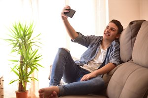Teen taking a selfie in living room
