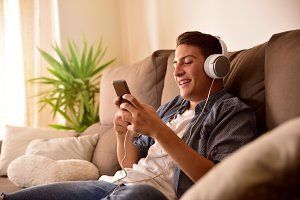 Teenager using mobile phone on couch