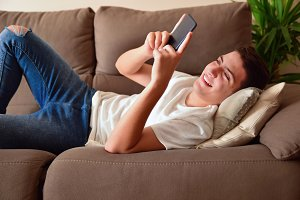 Young boy on couch consulting cell