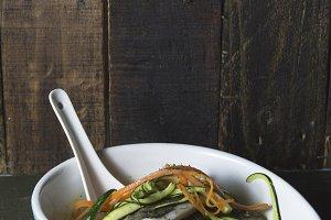 Hake and vegetable soup, on dark bac