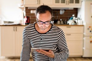 Young man in striped t-shirt with tablet at home.