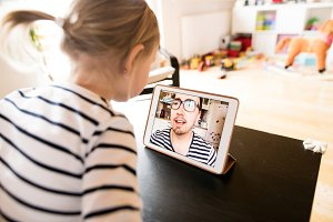 Little girl at home with tablet, video chatting with her father.