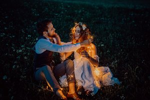 Beautiful bride and groom on a meadow at night.