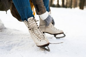Unrecognizable woman in winter clothes putting on old ice skates