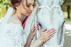 Bride stands near white horse