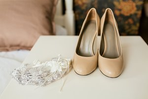 Beige shoes on a heels and lace garter on a white table. Wedding preparation. Artwork