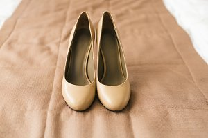 Beige shoes on heels of a bride on a brown textile background. Wedding preparation. Artwork.