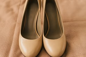 Beige shoes on heels of a bride on a brown textile background. Wedding preparation. Artwork.