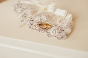 Golden wedding rings laying on lace garter on a white table. Wedding preparation. Artwork