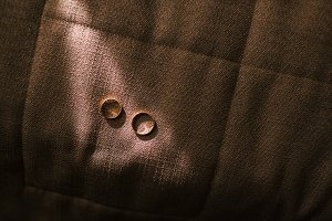 Golden wedding rings laying in sunlight on a dark textile background. Unusual Jewelry Photo. Wedding. Artwork